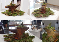 Photograph of sculpture of rusty anvil on bed of moss